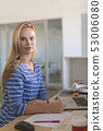 Female fashion designer looking at camera while working at desk  53006080