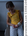 Girl sitting with fractured hand in clinic at hospital 53006164