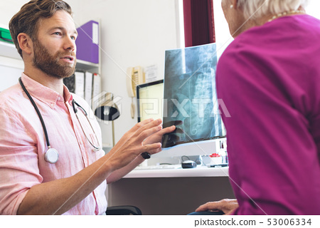 Male doctor showing x ray report to female senior patient in clinic 53006334