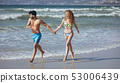 Couple holding hands and running on beach 53006439