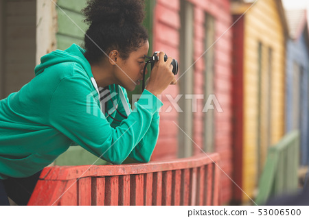 Woman capturing photograph while standing at beach hut 53006500