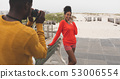 Man capturing photo of woman while standing at pavement  53006554