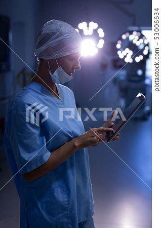 Female surgeon using digital tablet in operation room 53006634