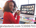 Female graphic designer with coffee cup looking at camera while sitting at desk  53006703