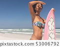 Female surfer with a surfboard standing on a beach 53006792