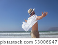 Happy man standing with open arm at beach 53006947