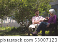 Senior woman talking with doctor outside on nursing home bench 53007123