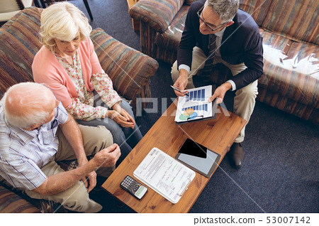 Physician showing medical statistics to senior couple 53007142