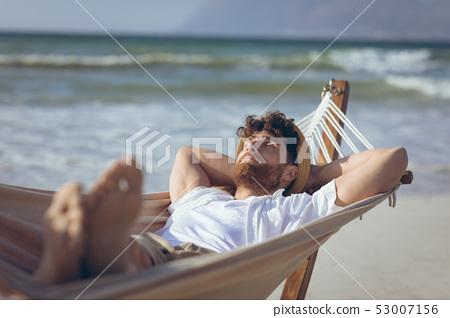 Man relaxing on hammock at beach 53007156