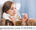 Sick young woman checking temperature 53009811