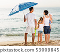 Man and woman with children standing with back to camera on beach 53009845