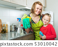 Girl helping mother dusting furniture 53010042