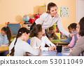 Teacher helping children drawing 53011049