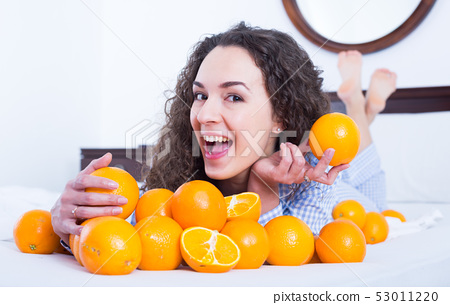 Positive girl eating oranges in bed 53011220