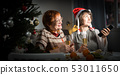 Happy mother and daughter drink champagne and watch TV on Christmas night 53011650