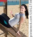 Positive woman training on beach by sea 53012738