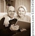 Senior spouses with picture album indoor 53013459