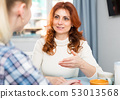 Mom and adult daughter talk and drink tea in the kitchen 53013568