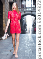 portrait of sexy young woman in red dress walking with shoes in hand in the old city 53014372