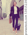 Businesswoman in suit with suitcase is going to the hotel 53015220