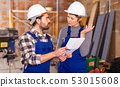 Disgruntled foreman discussing drawing with worker 53015608