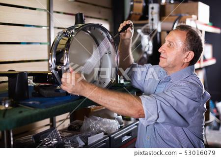 Adult music master is repairing music instruments in workshop. 53016079