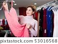 Woman choosing pretty dress 53016568