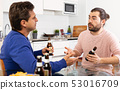 Drunk men sitting at table and drinking beer indoor 53016709