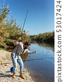Happy fisherman pulls fish out of the river 53017424