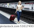 Girl using phone on subway station 53017493