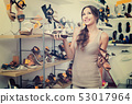 Portrait of woman looking confused with two pair of shoes 53017964