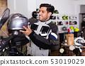 Male customer in new jacket is choosing modern helmet 53019029