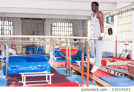 man in sportswear doing exercises on parallel bars 53019201
