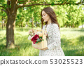 Half portrait of a charming positive woman dressed in long white summer dresses with a happy smile 53025523