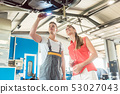 Auto mechanic checking the disk brake rotors of the car of a female customer 53027043