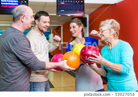 Happy family holding bowling ball 53027058