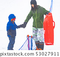 Mother is helping her boy to ride the sled 53027911