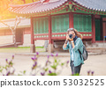 Travel to Seoul, South Korea, a young European girl traveler with a camera in hand in the palaces 53032525