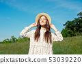 Beautiful sensual brunette in dress and hat standing with eyes closed in nature in bright back lit 53039220