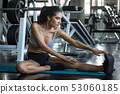 young fitness woman stretching her leg to warm up 53060185