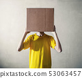 Person with overhead a cardboard box 53063457