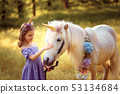 Girl in purple dress with wreath of a unicorn in hair hugging and kissing white unicorn. Dreams come 53134684