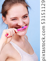 Woman brushing cleaning teeth 53151129