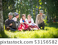 People in traditional Russian clothes sit on the lawn and talk - one of them plays the accordion and 53156582