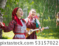 Two young attractive women in traditional russian clothes singing in the forest. One of them playing 53157022