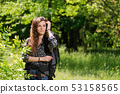 Beautiful tourist girl with huge black backpack 53158565