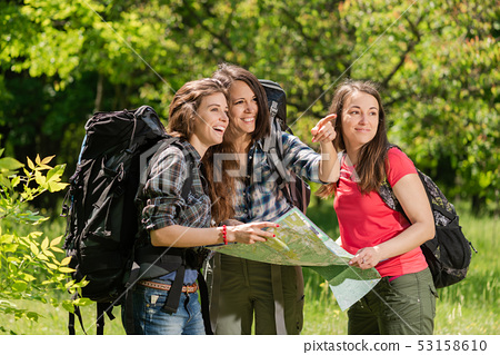 Tourist girls at forest with map and backpacks 53158610