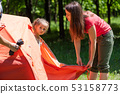 Small girl with mom set up camping tent 53158773