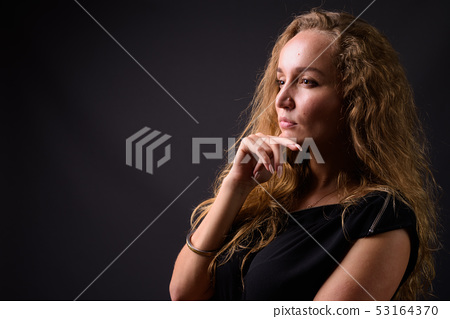 Profile view of young beautiful businesswoman with long wavy blond hair thinking 53164370