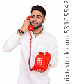Studio shot of young happy Indian man talking on telephone isola 53165542
